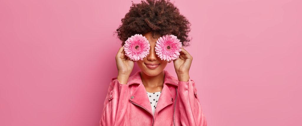 Una chica vestida de rosa y con dos margaritas en los ojos